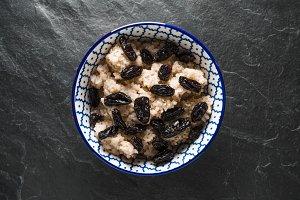 Useful barley porridge with raisins in a bowl on a gray stone