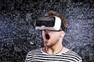 Double exposure. Man wearing virtual reality goggles. Blackboard