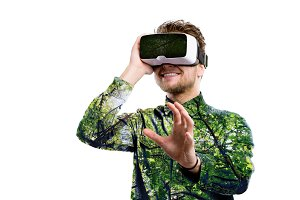 Double exposure. Man wearing virtual reality goggles. Trees.