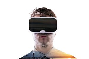 Double exposure. Man wearing virtual reality goggles. Sea at sunset.