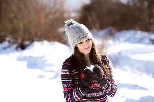 Beautiful young woman with cup of coffee in winter nature