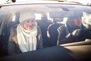 Senior couple in winter clothes driving a car