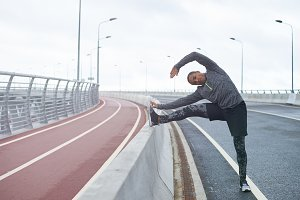 Candid shot of attractive fashionable young African male runner stretching legs and bending forward, touching toes after morning running workout session at stadium. Black athlete warming up outdoors
