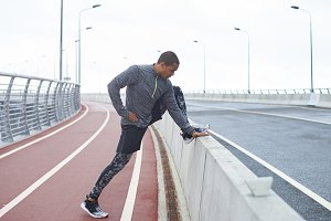 Outdoor lifestyle picture of confident young black male runner preparing for cardio workout, stretching legs on road railing while exercising outdoors, wearing trendy training shoes and clothes