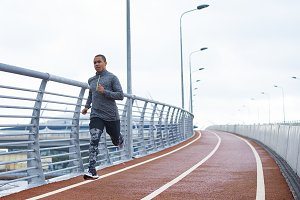 Healthy active lifestyle concept. Attractive young African male jogger exercising at stadium alone early in the morning. Muscular dark-skinned sportsman in trendy outfit, getting ready for marathon