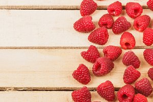 Red raspberries on the light wooden background