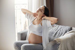 Grumpy mother tired of her pregnancy. Keeping motivated staying alone at home is hard. Easing her neck and back strain.
