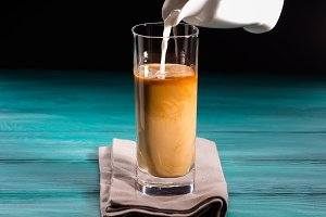 Glass of iced coffee. Pouring milk