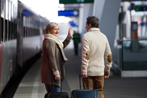 Senior couple on train station pulling trolley luggage.