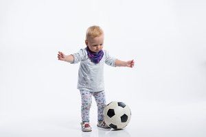 Cute little girl playing with soccer ball. Studio shot.
