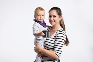 Beautiful mother holding baby daughter in her arms. Studio shot.