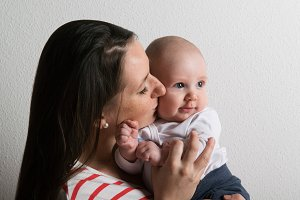Beautiful mother holding baby son in her arms. Studio shot.