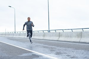 Sports, people, strength, endurance and determination. Full length outdoor portrait of confident young African American sportsman in stylish outfit running fast along empty road, training for marathon