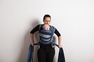 Beautiful young mother wrapping her son into sling. Studio shot.