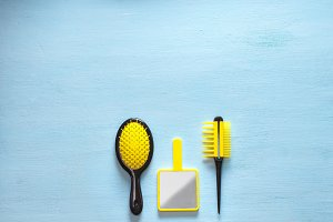 Two yellow hair comb crest brushes with handle for all types, and mirror isolated on blue copy space background. Minimalistic feminine flat lay