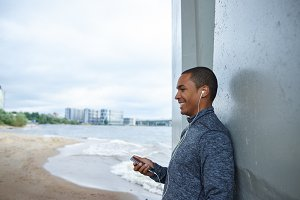 Attractive joyful young African male using headphones and mobile while talking to his girlfriend, having rest at grey wall by he sea after morning run outdoors. People, technology and active lifestyle