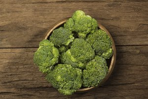 Raw broccoli on wooden bowl