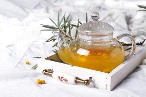 A glass teapot with sea buckthorn