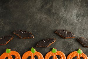 Halloween pumpkin and bats cookies overhead shot with copy space. On dark concrete background