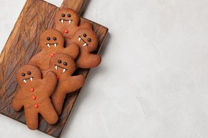 Homemade ginger biscuits in the shape of gingerbread men for Halloween. On the lighter concrete background. Top view with copy space