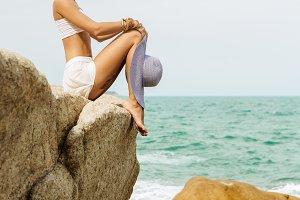 Beautiful woman sit at stone beach.
