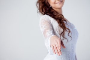 The bride extends her hand, beautiful smiling woman in a wedding dress