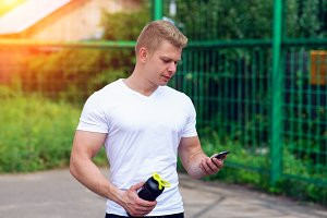 The man is watching timer on the phone, social networks, hand a shaker, a bottle of a vault, a protein. In summer city. The concept of a healthy lifestyle. In the smartphone watching video.