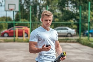 The man is watching timer on phone, social networks, hand a shaker, bottle of vault, protein. In summer city. The concept healthy lifestyle. In smartphone watching video. Background of cars in park.