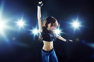 young girl dancing on the background of bright lights