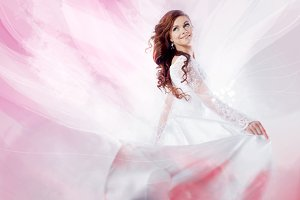 Beautiful bride in wedding dress,  abstract soft pink background