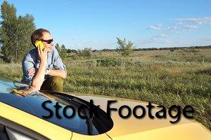 Man is talking on phone near car