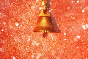 Golden Christmas bell on red texture