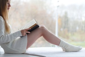 woman in warm sweater read book