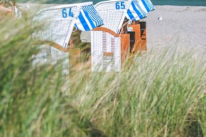 Roofed wooden chairs on sandy beach in Travemunde, baltic sea, Germany