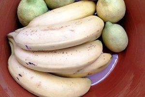 Bananas and lemons on clay pot