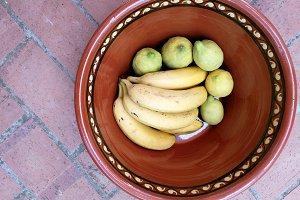 Lemons and bananas on clay pot