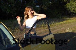 Girl talking on phone near car