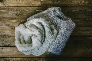 circular wool scarf and gray knit sweater over rustic wood