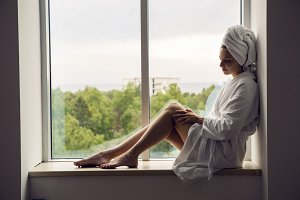 girl in a Bathrobe and towel on head sits on the window