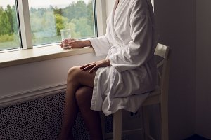 girl in a bathrobe and towel on head sitting