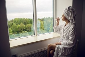 girl in a bathrobe and towel on head sitting