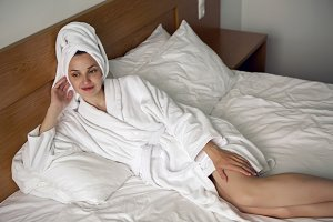 girl lying in bed in a Bathrobe at home