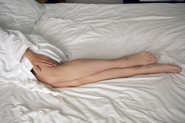 girl lying in bed in a Bathrobe at…