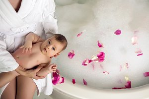 mom in a robe sitting on a round bathtub