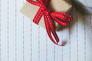 Gift box, wrapped in recycled paper and red bow on on white tablecloth