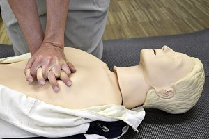 Man practicing CPR techniques on dummy.