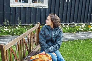 woman sitting on a bench near a wooden village house
