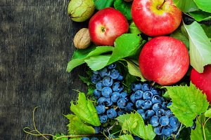 Assortment organic fruits berries apple grape damascene walnut dark wooden country background health care natural concept top view