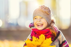 Happy little girl with autumn leaves