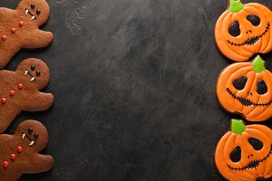 Homemade gingerbread cookies for Halloween in the form of pumpkins and gingerbread men vampire on dark concrete background with copy space. Top view